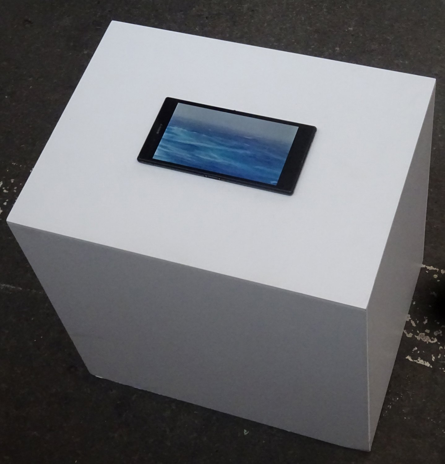 Sean Snyder Tableau Bateau,2016 random video loop with audio on hacked Sony XPERIA Z Ultra, displayed on PVC structure, RAL 9003, 40 cm high x 40 cm wide x 30 cm deep
